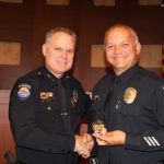 Surprise Police Chief Terry Young congratulating Sergeant Jesus Galaz