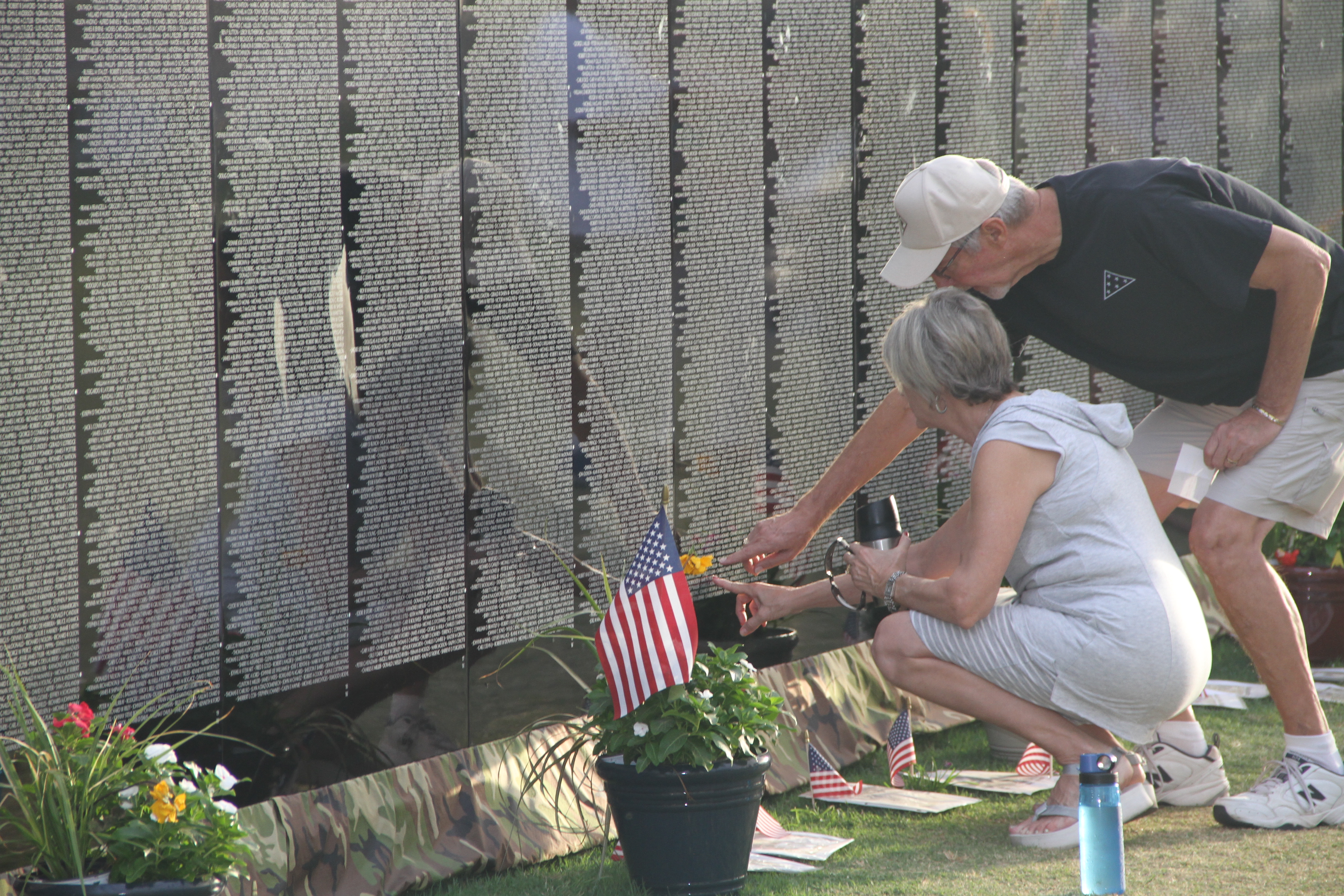 A couple visiting and reading names on the Vietnam Memorial Moving Wall