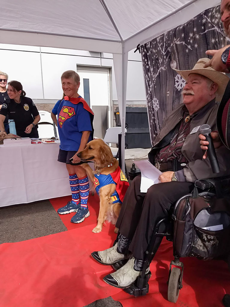 "A participant of the ""Most Like My Owner"" Dog Competition and Fashion Show, with their dog, dressed in Superman costumes."