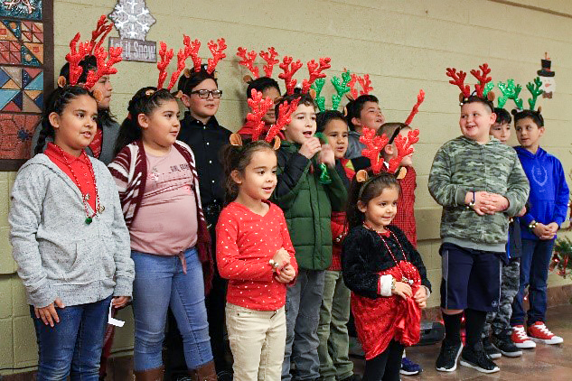 Young residents wear red and green reindeer antlers.