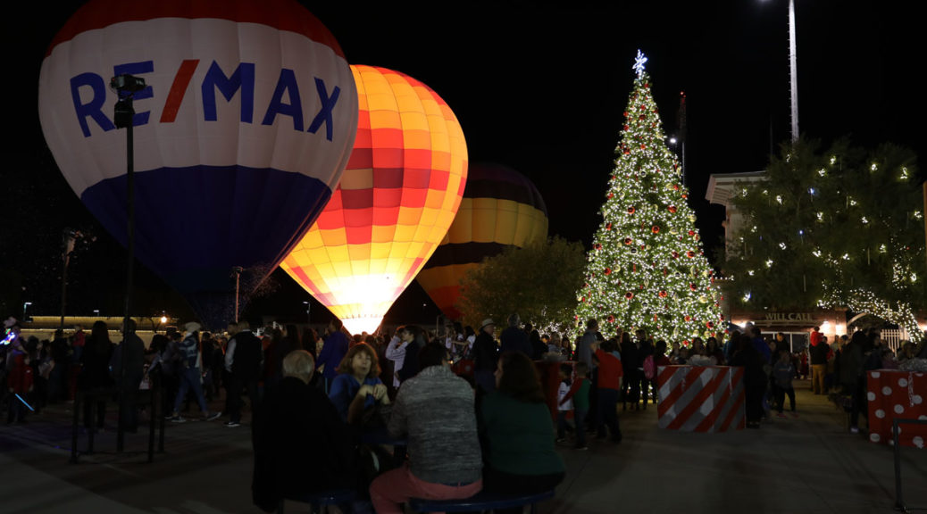 An illuminated Christmas tree and hot air balloon at night.