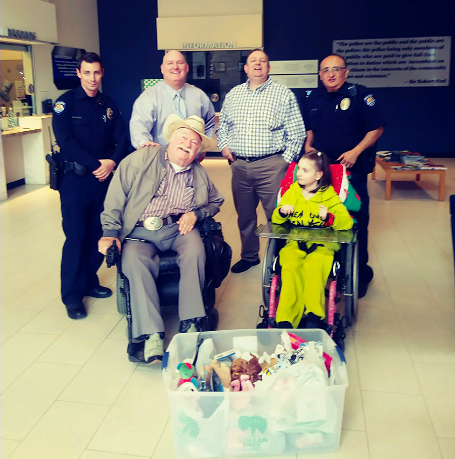 Vice Mayor Winters, resident Charles Collins and his daughter, and Surprise Police Officers with a box of donations for Toys for Tots.