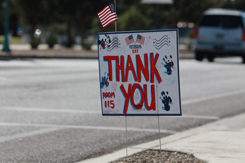 A Veterans Day Thank You sign decorated with children's handprints.