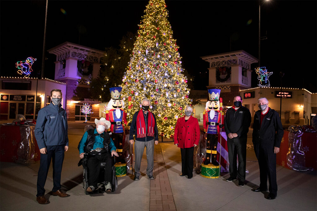 Surprise City Council stands in front of a lit Christmas tree at Surprise Stadium.