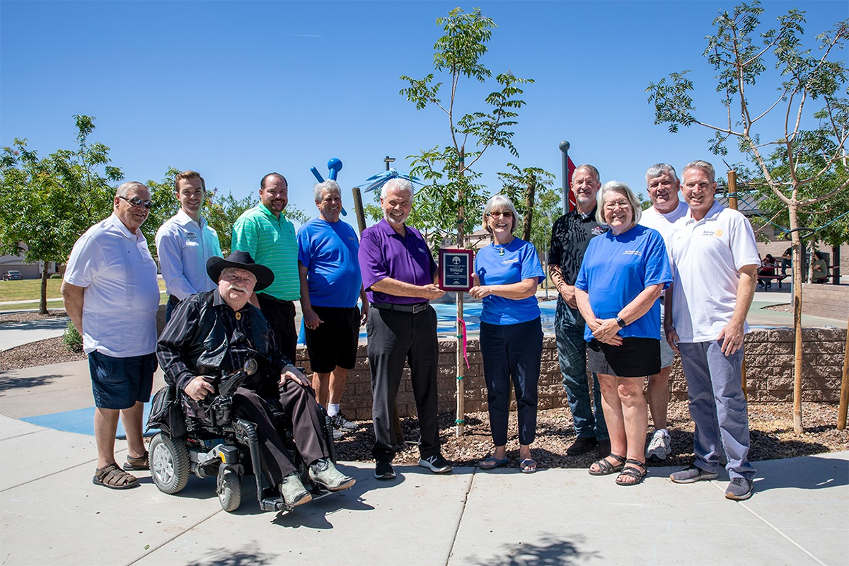 Surprise City Council and Rotary Club of Surprise hold a plaque in front of a newly planted tree.