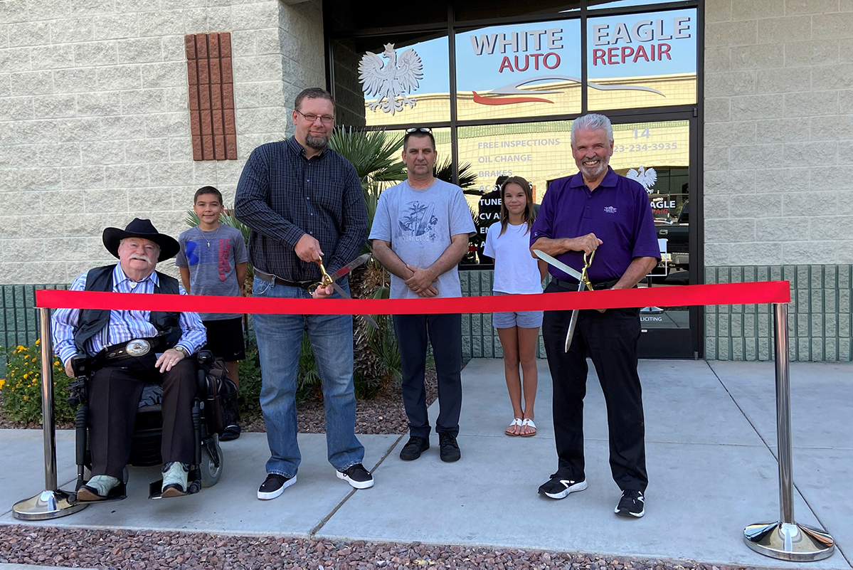 Mayor Hall cuts a red ribbon outside of White Eagle Auto Repair for their grand opening.